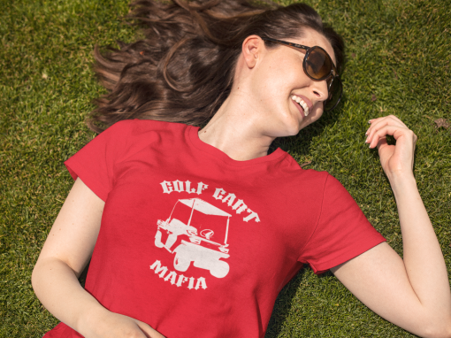smiling woman lying down on the grass while wearing a round neck t shirt template and sunglasses a15916